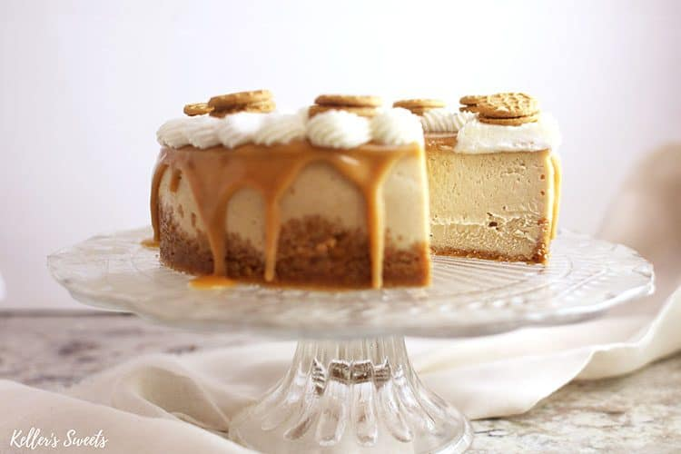 Instant Pot Nutter Butter Cheesecake with a slice missing on a clear cake stand