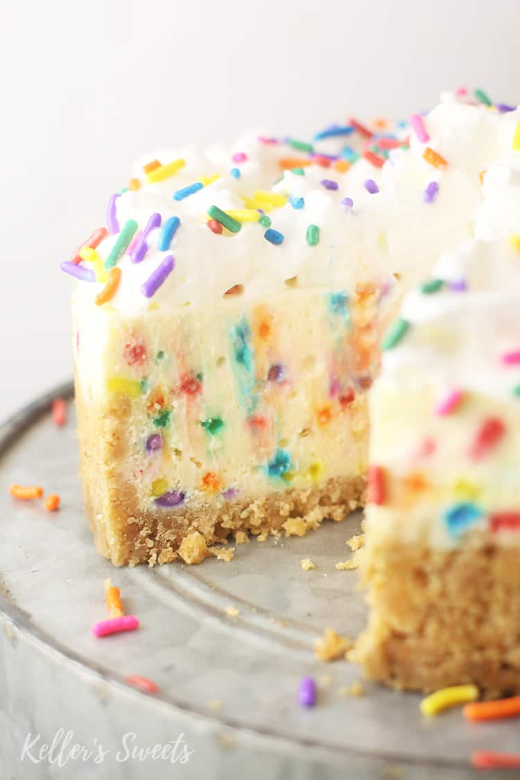 sliced Instant Pot Funfetti Cheesecake on a silver cake stand