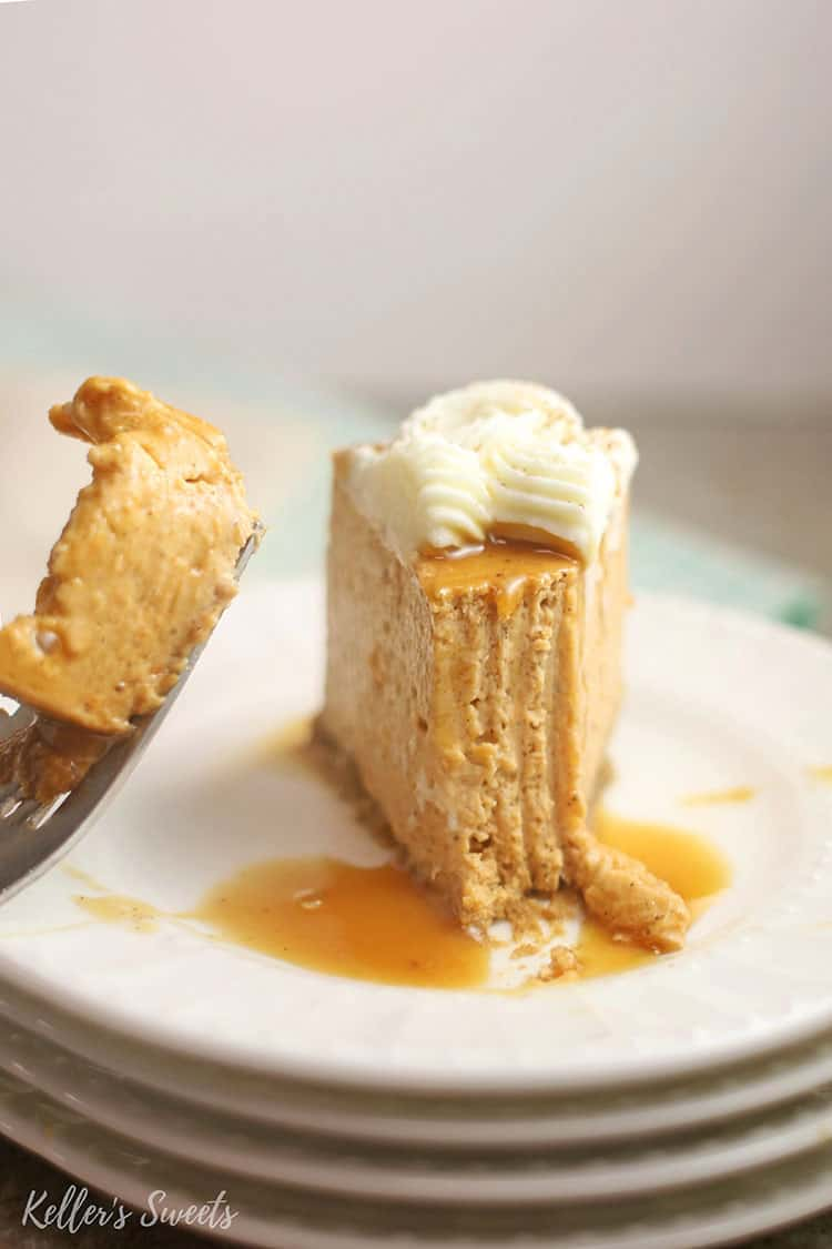 slice of Instant Pot Pumpkin Pie Cheesecake with bite missing on white plate