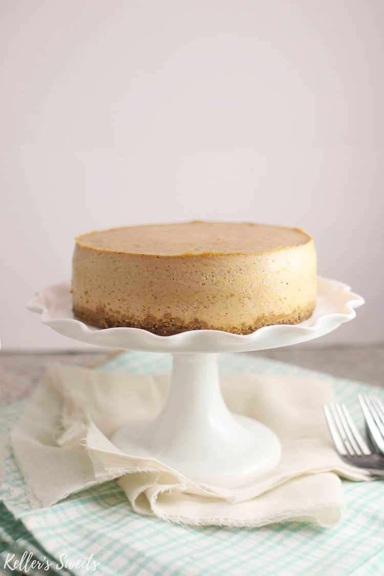plain Instant Pot Pumpkin Pie Cheesecake on white cake stand
