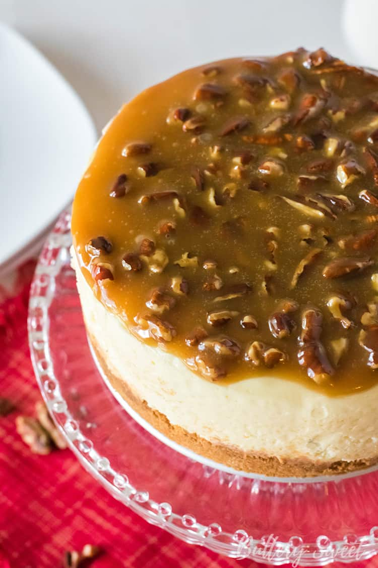 Instant Pot Praline Cheesecake on a cake plate with praline caramel topping