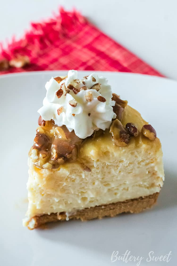 A slice of Instant Pot Praline Cheesecake with caramel, pecans and whipped cream
