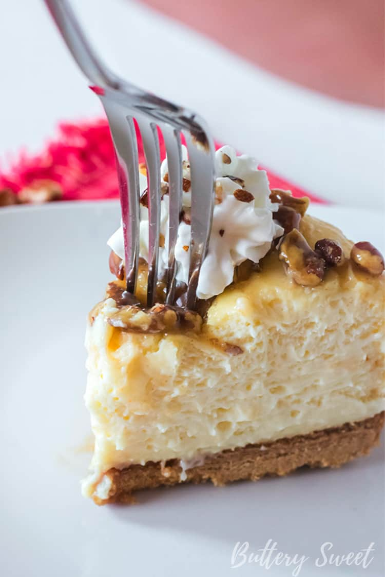 A fork removing a bite of Instant Pot Praline Cheesecake from a slice