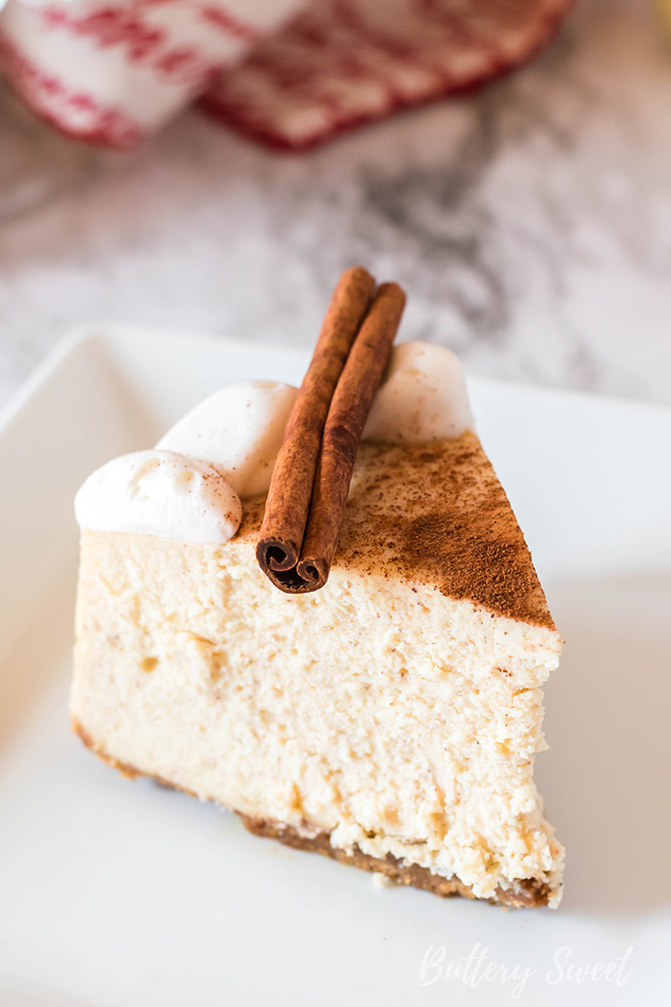 slice of Instant Pot Eggnog Cheesecake dusted with cinnamon and garnished with cinnamon stick on white plate