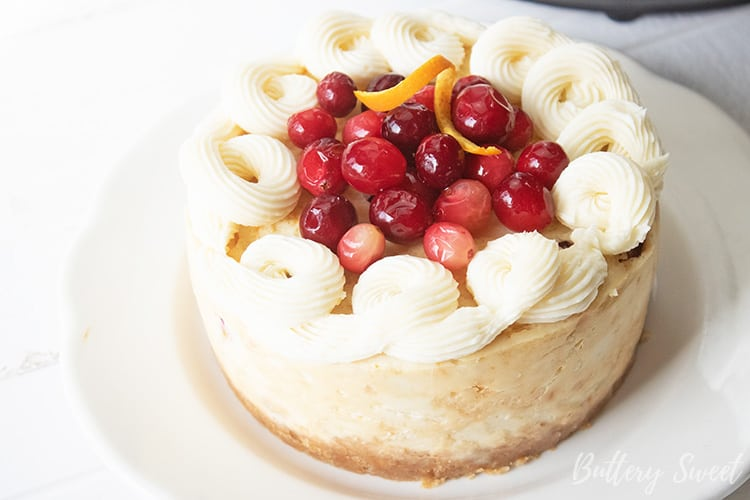 Instant Pot Cranberry Orange Cheesecake topped with cream cheese frosting and fresh cranberries.